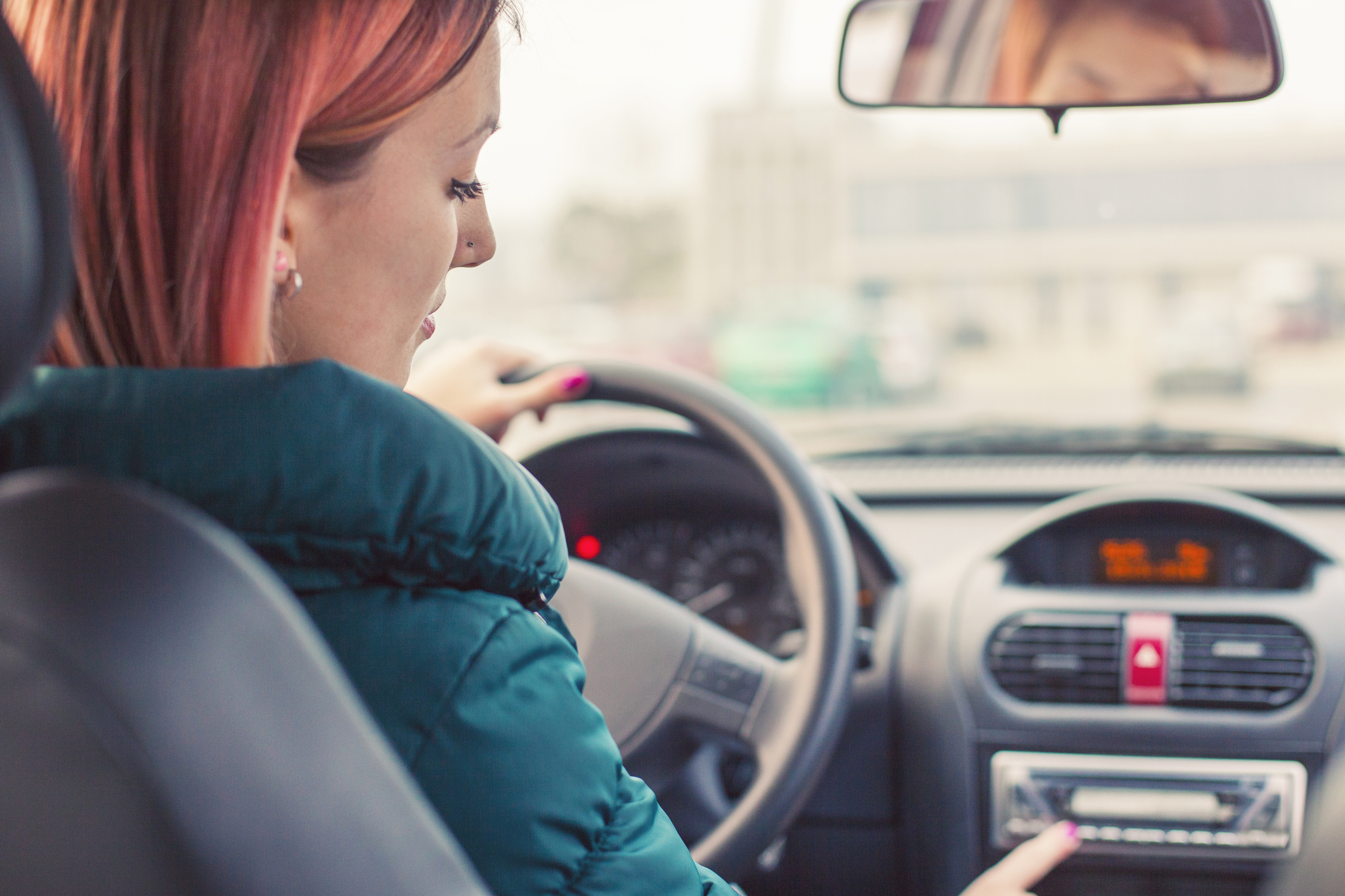 Woman in car pushing radio buttons