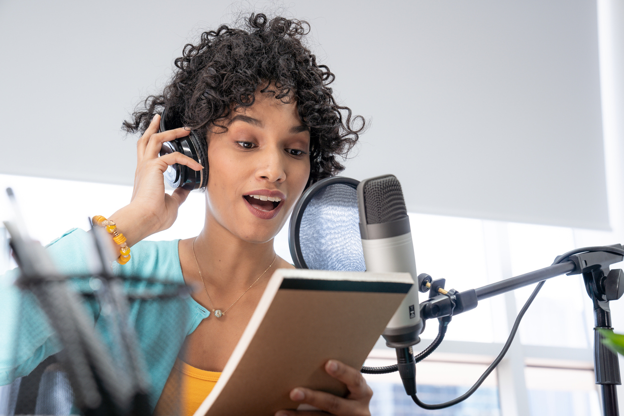 women reading into a microphone