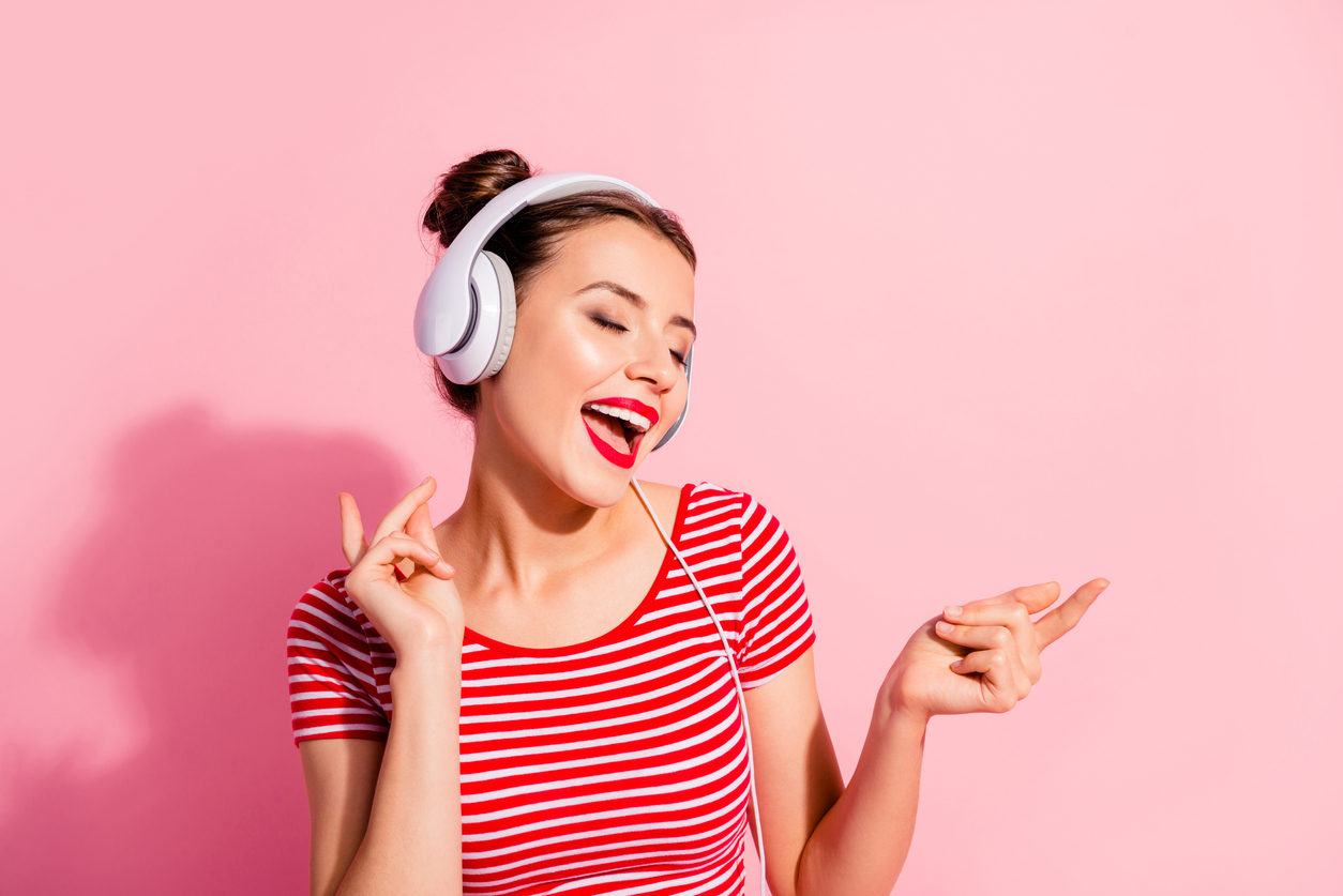 Woman with white headphone on singing. She is wearing a pink shirt with a pink photo background