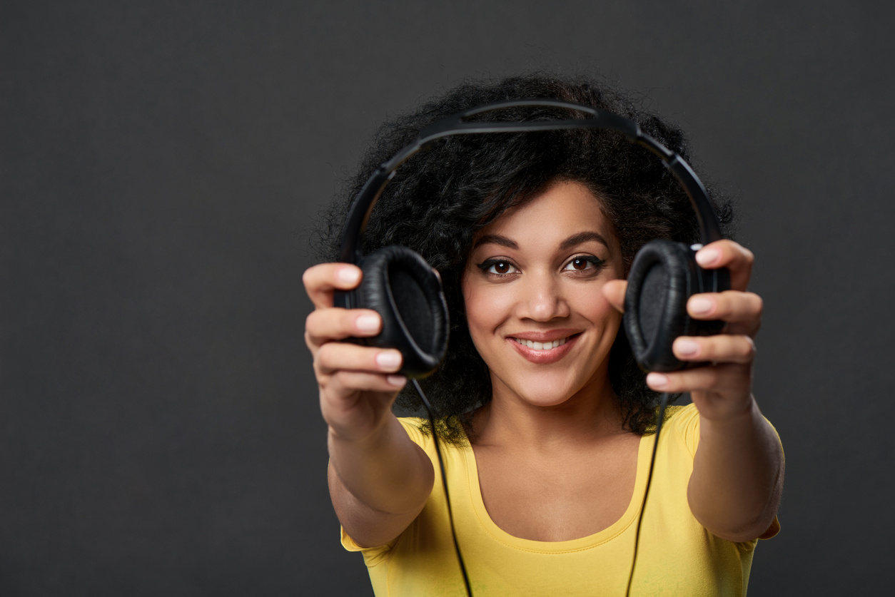 Mixed race woman smiling in a yellow shirt as she hands you headphones.