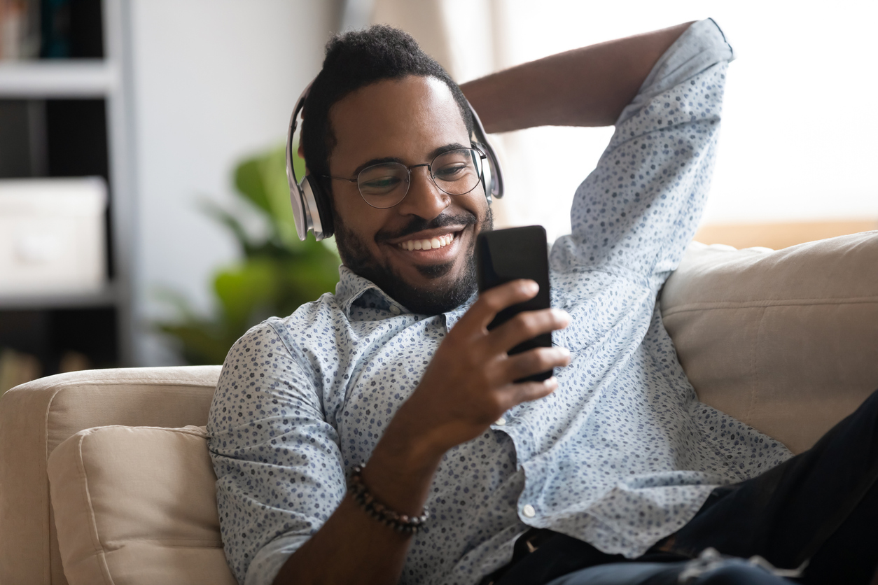 Smiling African American man wearing headphones and smiling at his phone.