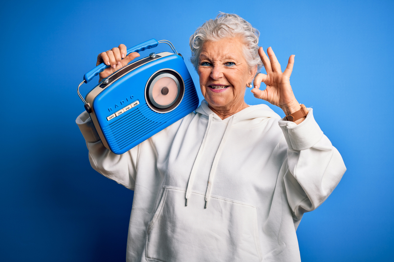 "Elderly woman smiling in a white sweatshirt with a blue background. She is holding a blue old school radio while giving the ""ok"" sign with her fingers."