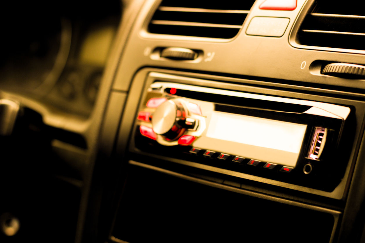 Close up of a car radio system. The image is slightly blurry with red lights.