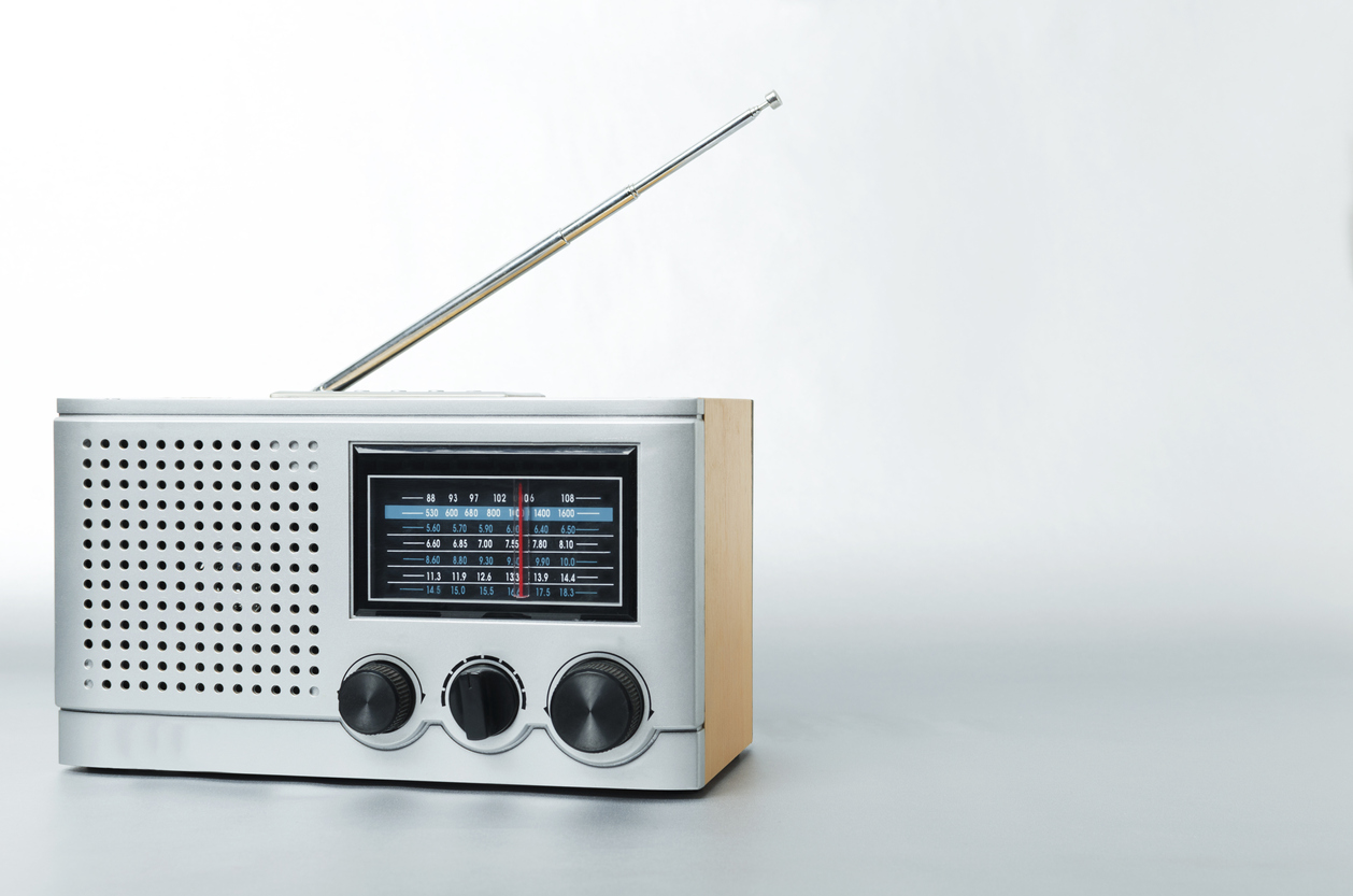 Old type of radio with fm channels and antenna on the gray background