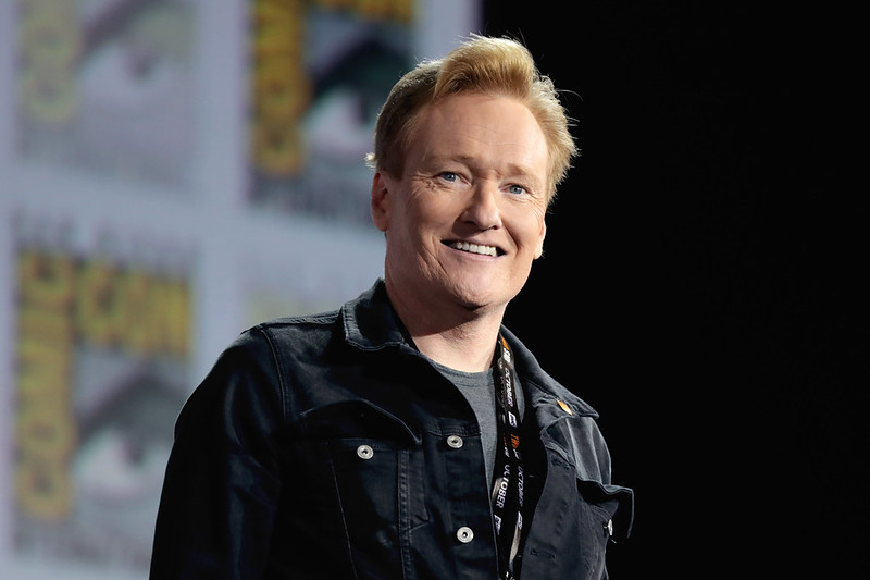Conan O'Brien at Comic Con. He is pictured from the chest up and is smiling while wearing a black jacket.