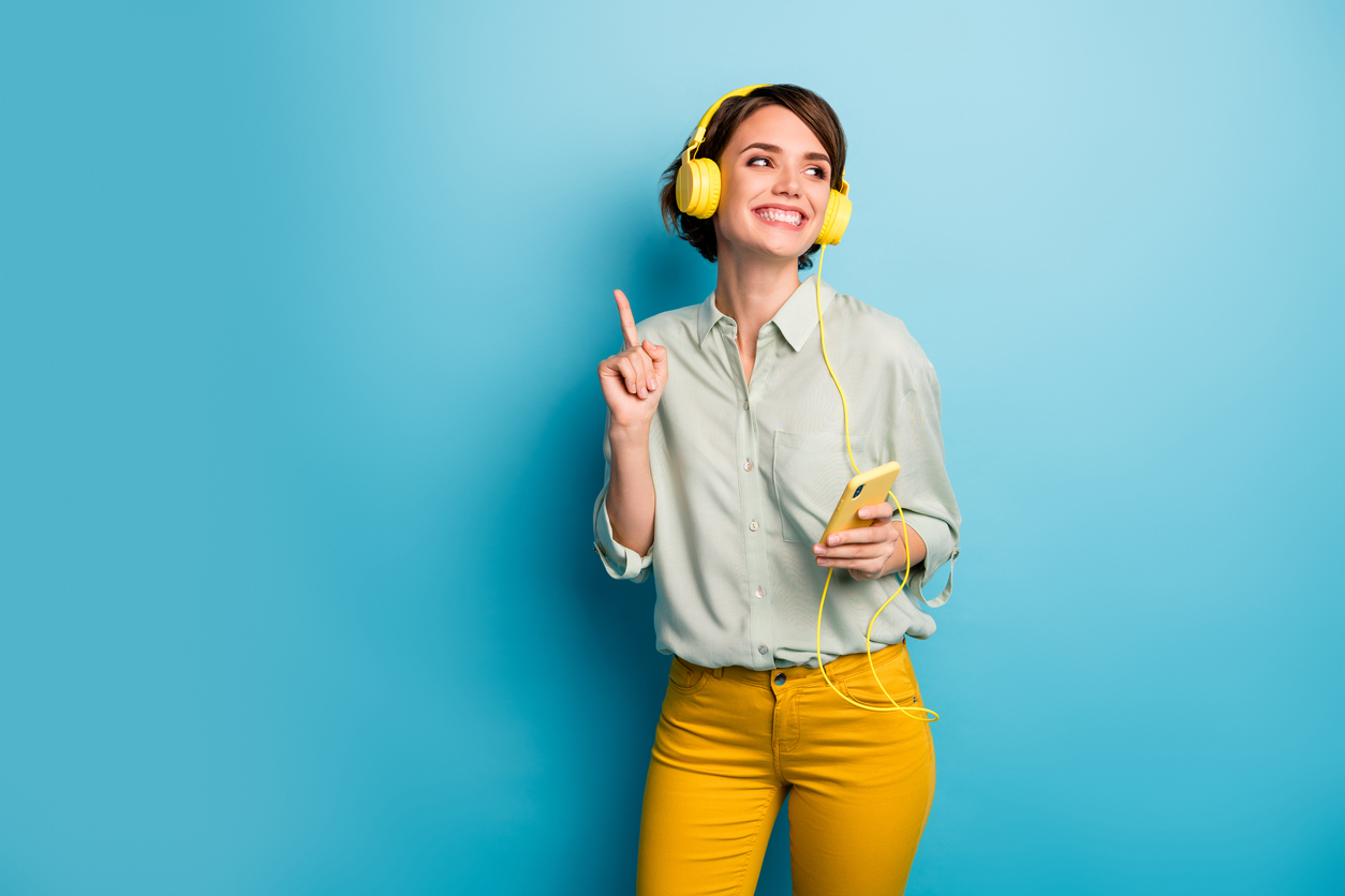 woman in yellow pants and a light blue top dancing. She's wearing yellow headphones and standing in front of a blue background.