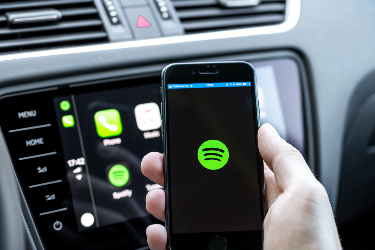 Hand holding a phone in the car with the spotify logo on the phone screen