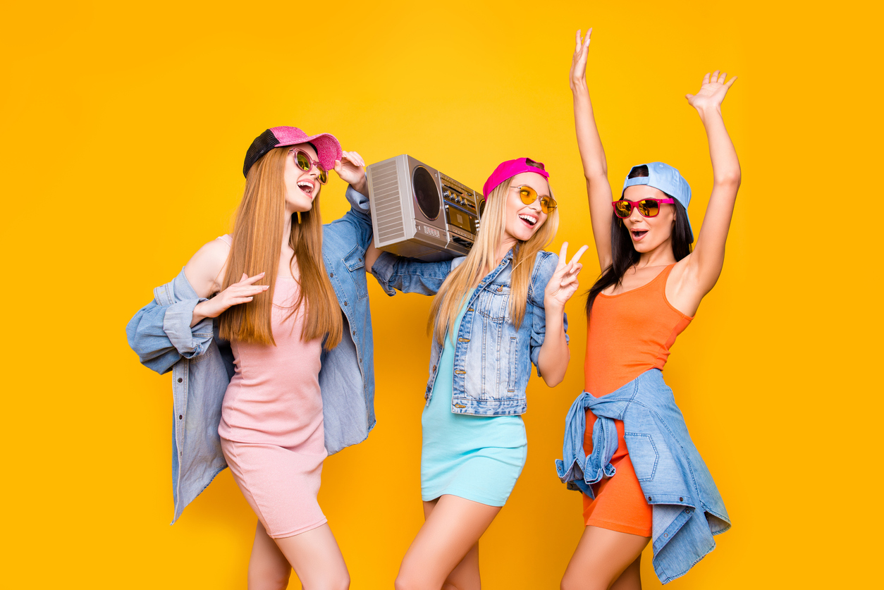 Three girls dancing against a yellow background. They are all wearing baseball hats and one is holding a large stereo.
