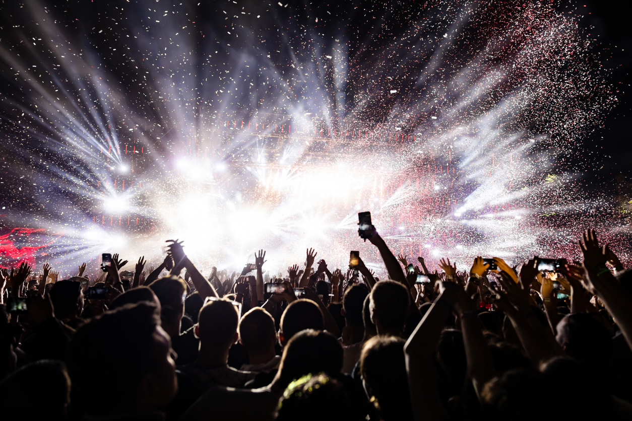 Audience watching confetti fireworks and having fun on music festival at night.