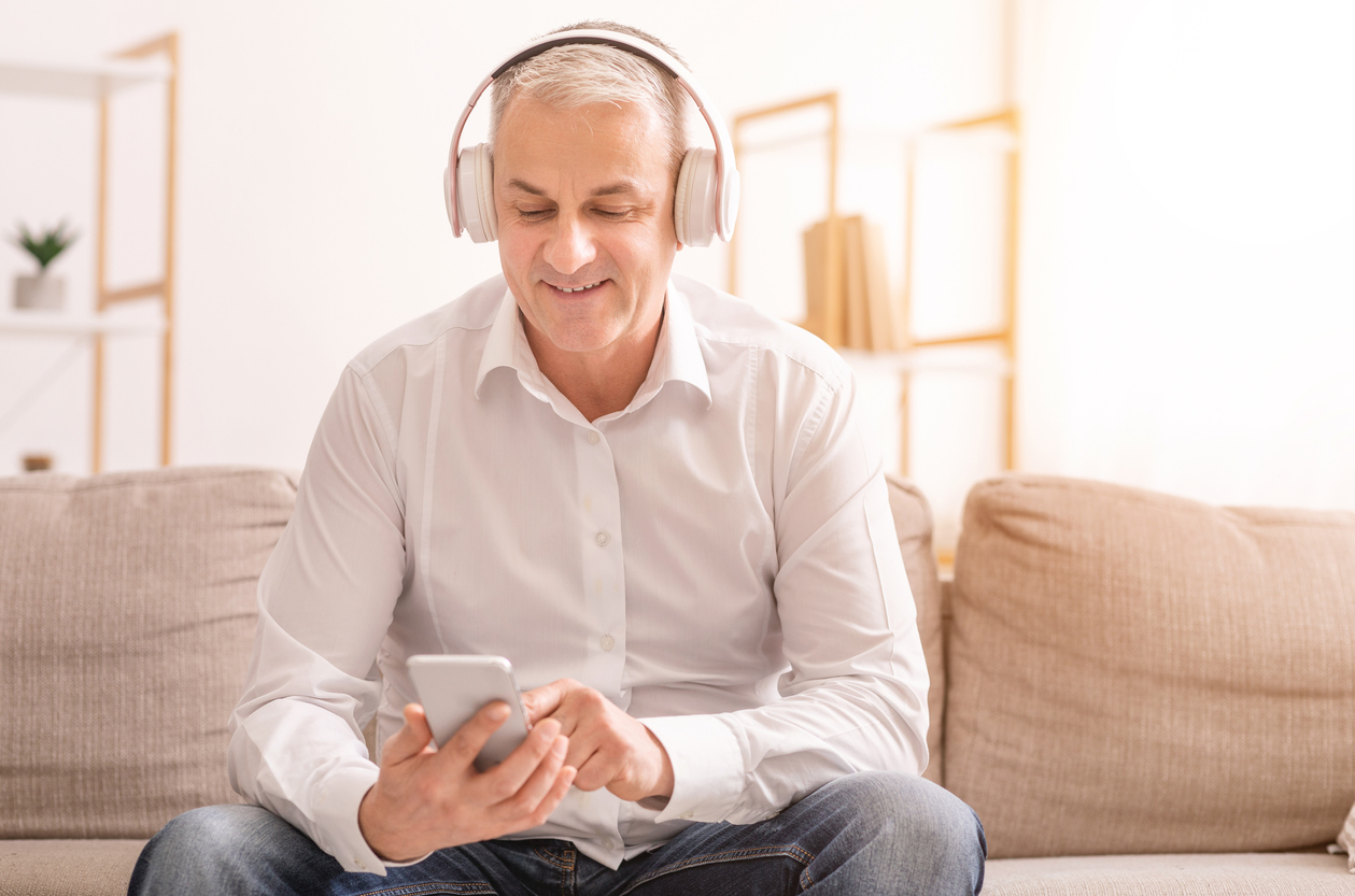 Man in headphones listens to a podcast on his smartphone.