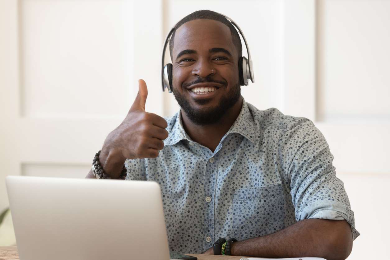 Man sitting in front of computer smiling at the camera with a thumbs up.