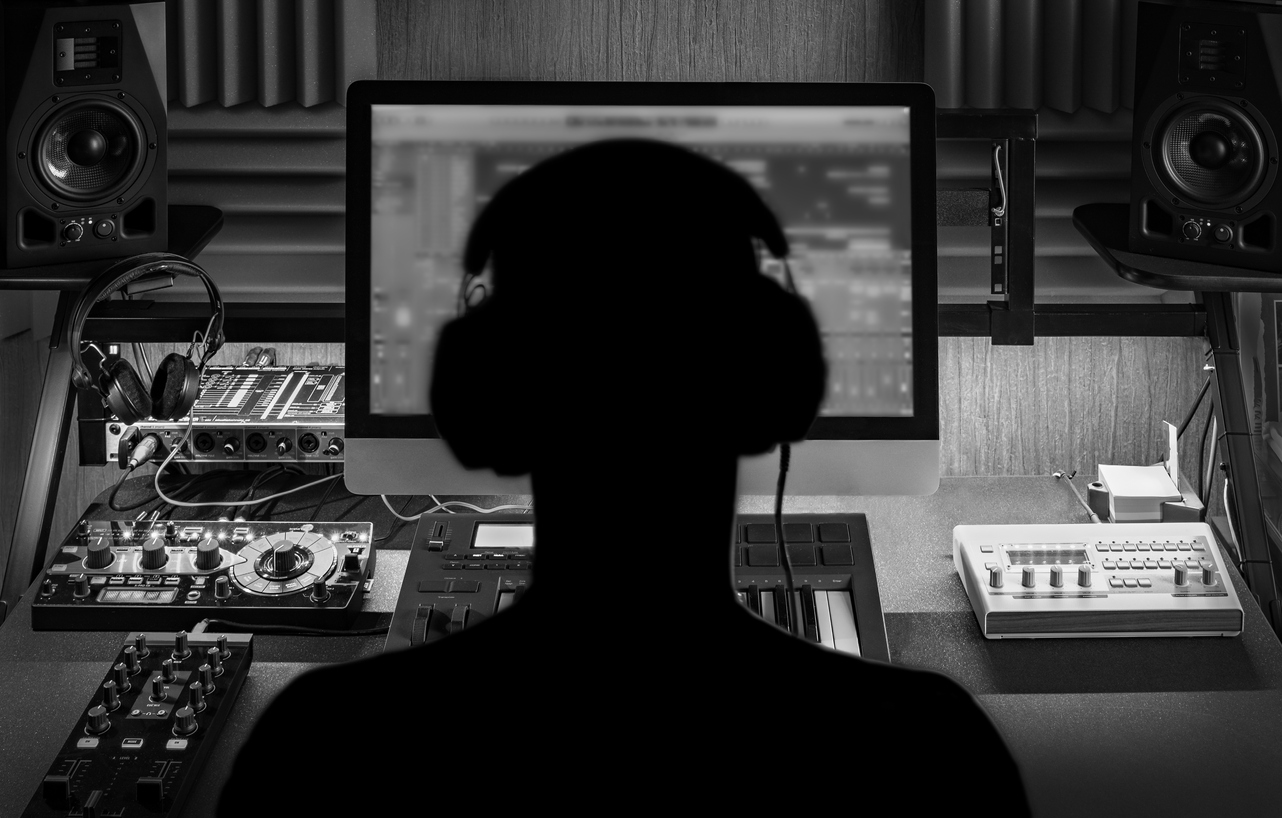 View of someone from behind sitting at a computer with headphone on. The image is in black and white.