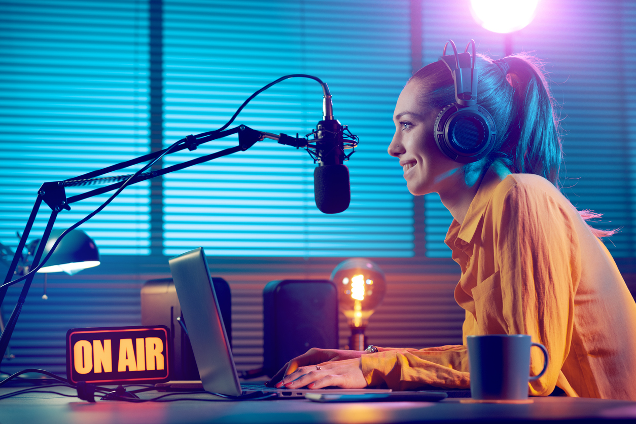 Woman smiling inside of a radio studio as she speaks into a microphone.