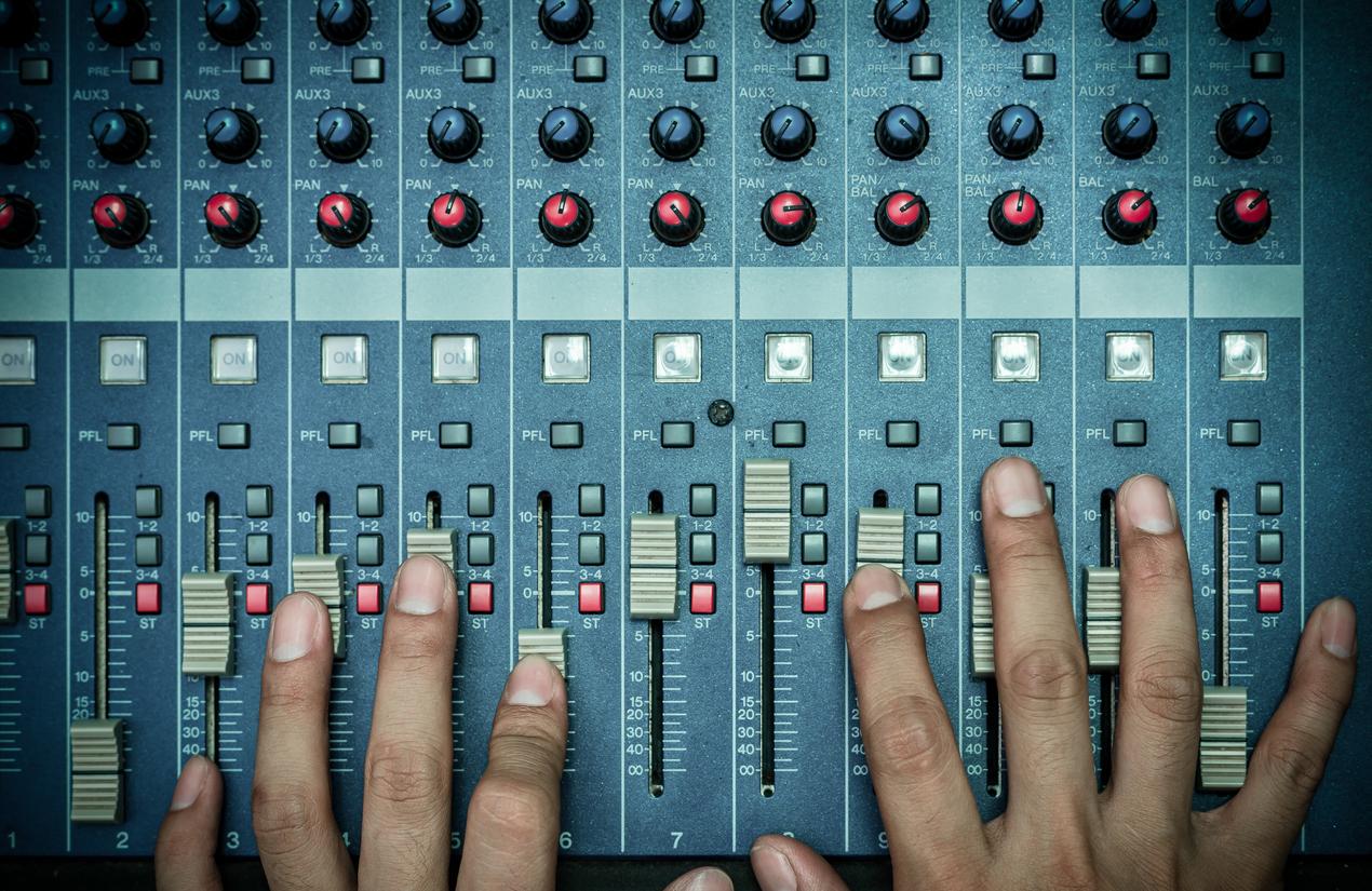 Top view of Hands adjusting audio mixer.