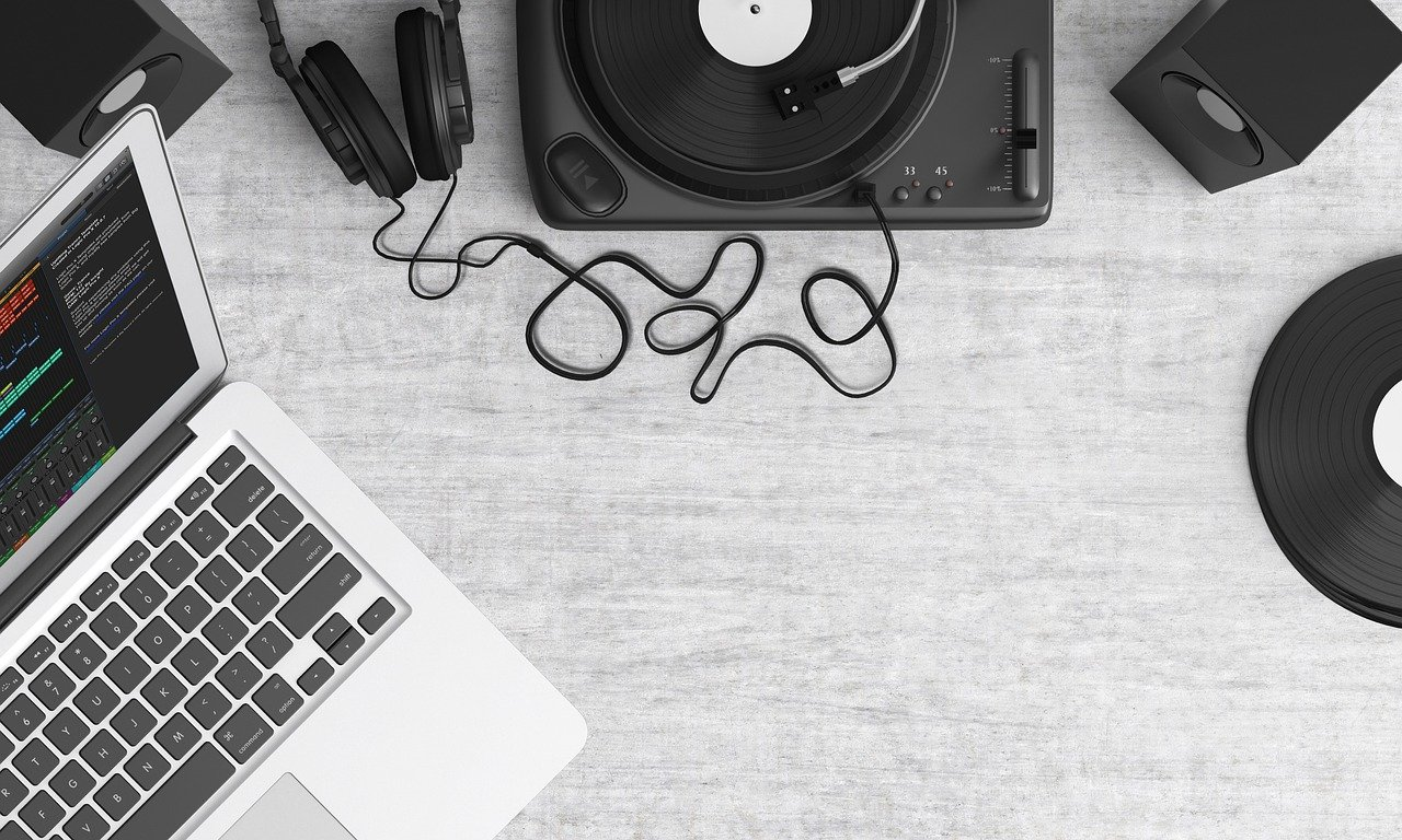 Overhead view of a grey desk that has a laptop, turntable, record, and headphones on it.