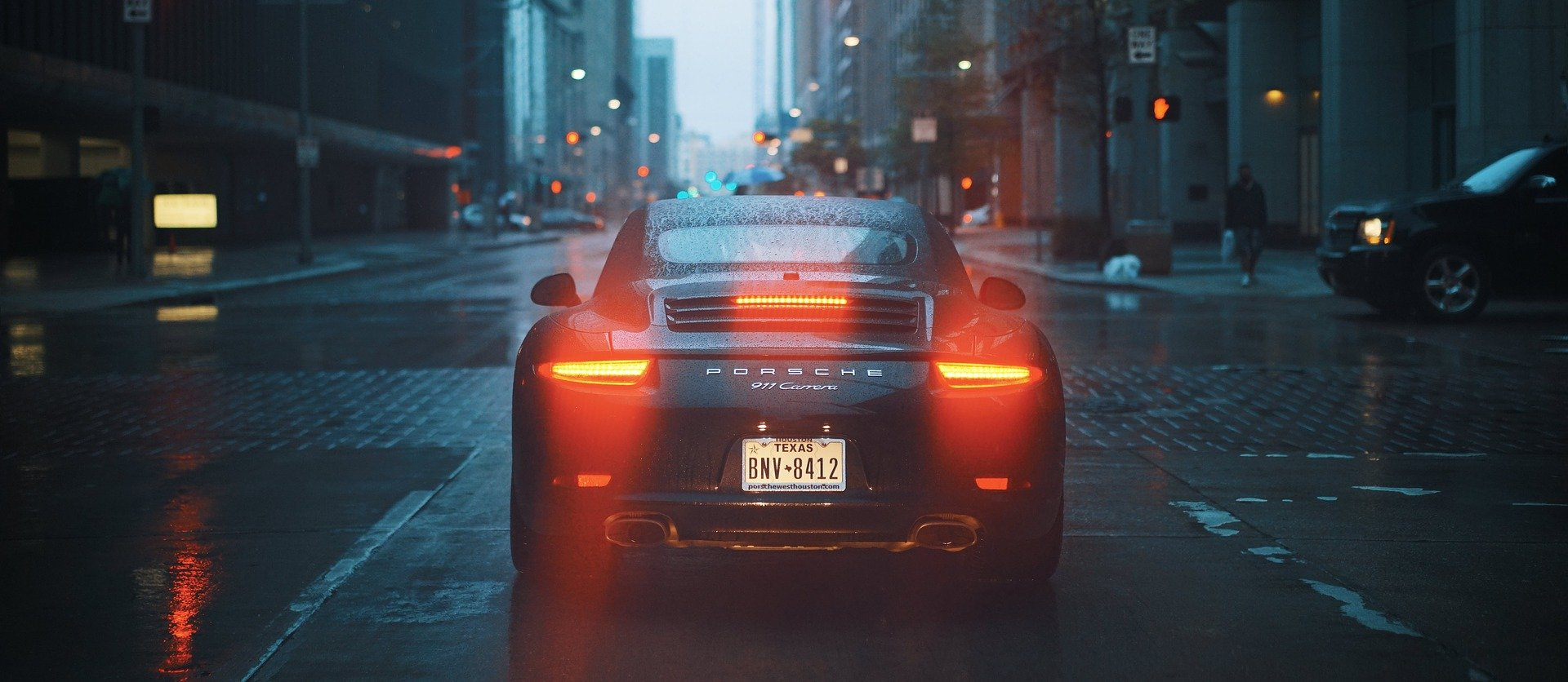 Back view of a porche driving through a city at night.