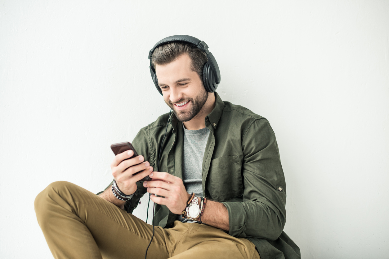 Man sitting down smiling at his phone. He is wearing tan pants, a green jacket, and has headphones on.