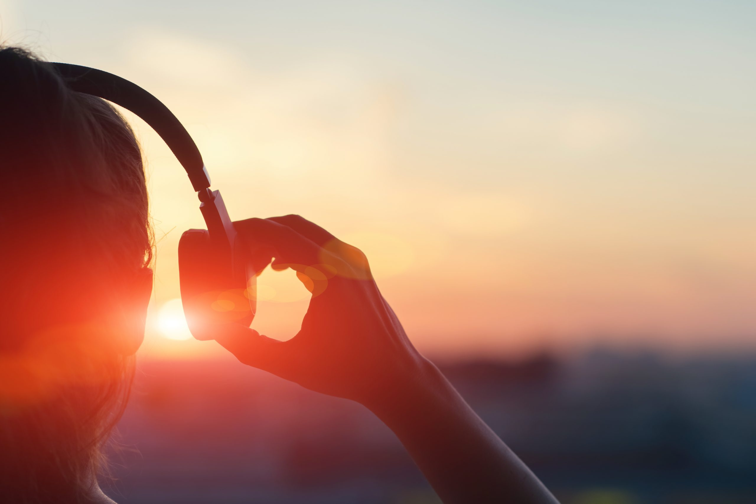 half of a head wearing headphones as they watch the sunrise
