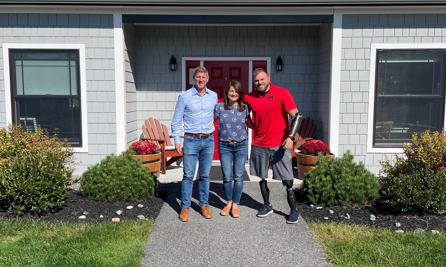 Jeff Small with Travis Mills and his wife outside.