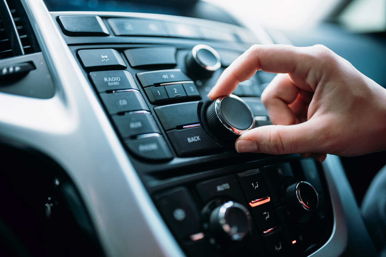 Closeup of a hand turning the volume dial on a car radio.