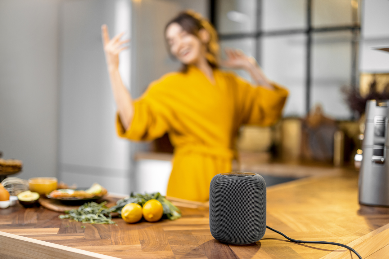Smart speaker on a kitchen island. There is a woman in yellow dancing in the background.